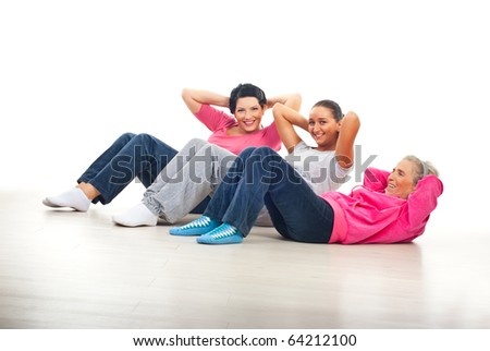 Laughing happy women having fun and doing abs on floor over white background