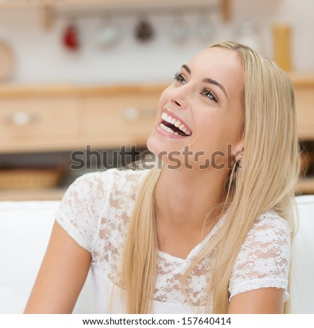 Laughing happy young blond woman sitting on a couch in the living room looking up with a joyful smile - stock photo