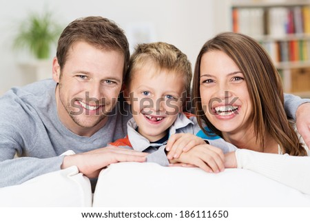 Laughing happy young family posing together in the living room with an adorable young boy with missing front teeth flanked by his attractive smiling parents - stock photo