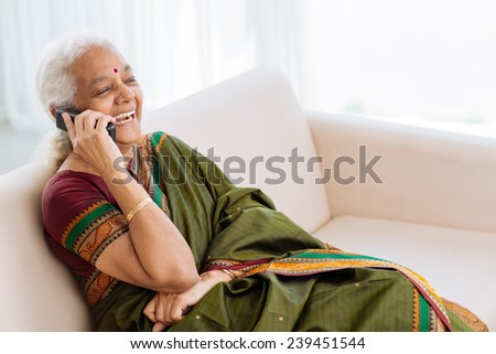 Laughing Indian woman with a telephone sitting on the sofa - stock photo