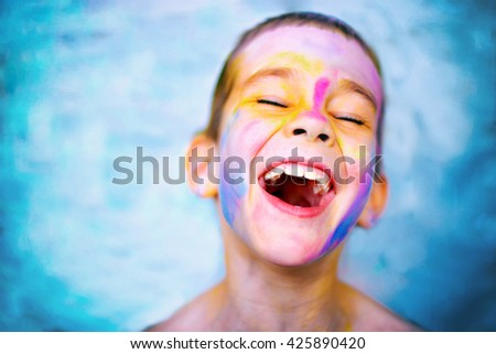 laughing kid with paint stained face. boy laughs cheerfully enjoying active games and creativity. head thrown back, eyes closed. copy space for your text - stock photo