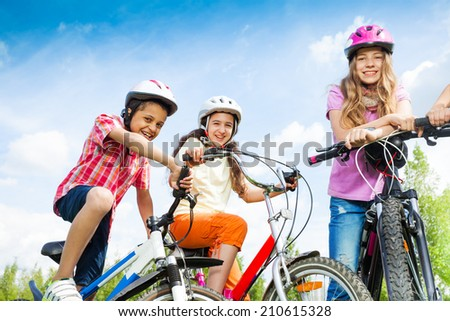 Laughing kids in helmets hold bike handle-bars - stock photo