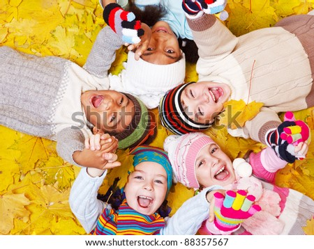Laughing kids on autumnal leaves