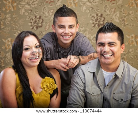 Laughing Latino family with son, mother and father - stock photo