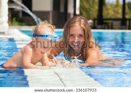 Laughing little baby boy in underwater goggles with happy mother having fun in pool before swimming lesson. Healthy lifestyle, water sport activity with active parents on family vacation with child.