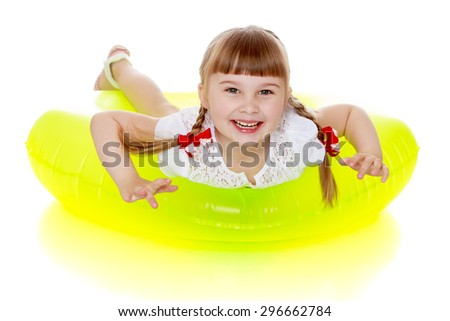 Laughing little blonde girl with short bangs and long fun braided pigtails lies on the yellow rubber ring for swimming in the sea , the girl is preparing to go on vacation - isolated on white - stock photo
