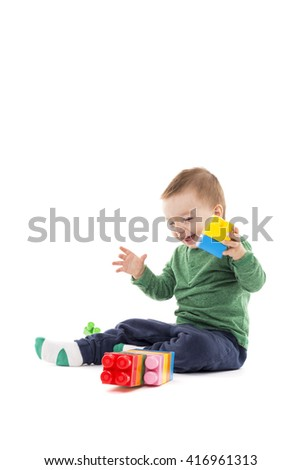 Laughing little boy playing with colorful blocks isolated on white background