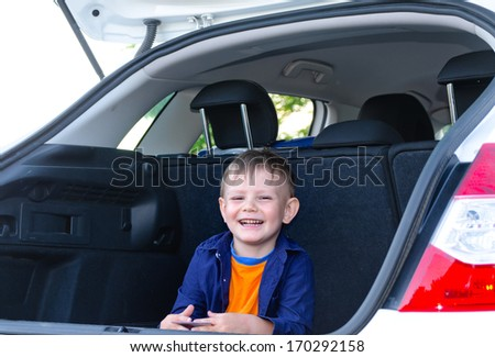 Laughing little boy sitting in the back of a car with the boot open grinning happily at the camera as he waits to set off on a journey - stock photo
