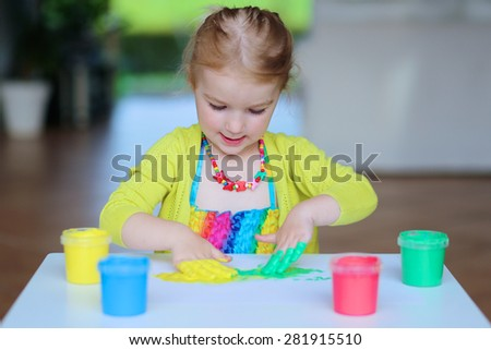 Laughing little child, blonde artistic toddler girl painting and drawing with colorful finger paints indoors at bright room at home or kindergarten. - stock photo