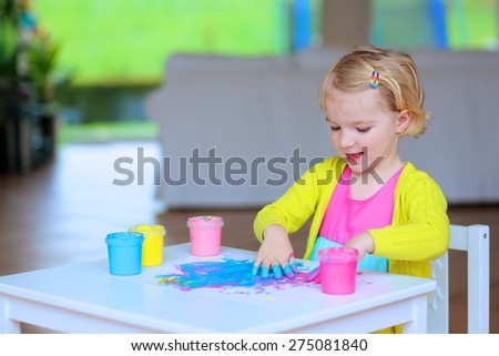 Laughing little child, blonde artistic toddler girl painting with colorful finger paints indoors at bright room at home or kindergarten - stock photo
