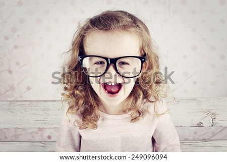 Laughing little funny girl wearing glasses - stock photo
