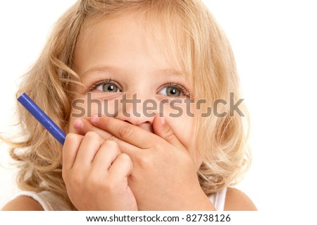 Laughing little girl covers her mouth with her hands and holding a pencil in her hand close-up on  white background - stock photo
