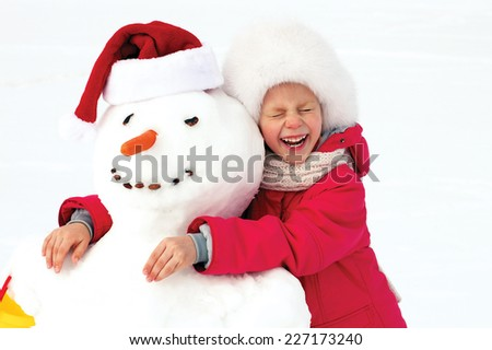 laughing little girl hugging a snowman - stock photo