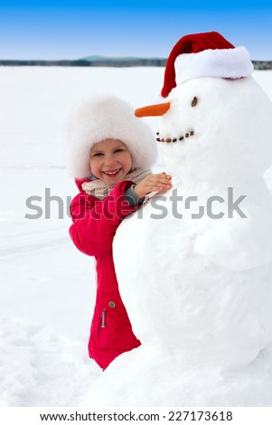 laughing little girl hugging a snowman. vertical - stock photo