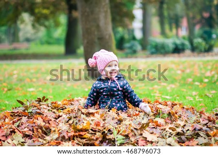 laughing little girl playing with leaves in the autumn park