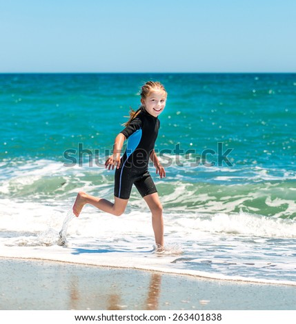 laughing  little girl runing in a wetsuit on the seashore - stock photo