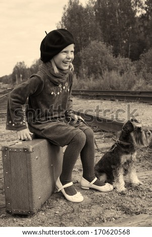 laughing little girl sitting on a suitcase on the railroad with his dog - stock photo