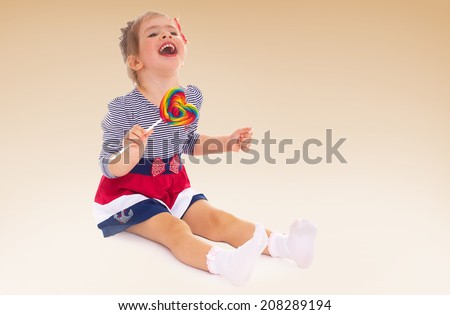 Laughing little girl sitting on the floor and eating a lollipop.kindergarten, the concept of childhood and joy, teens - stock photo
