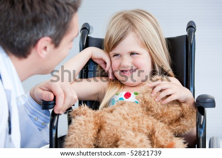 Laughing little girl sitting on the wheelchair at the hospital - stock photo