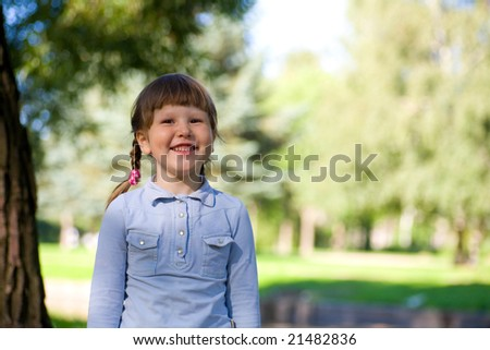 Laughing little girl standing near the tree
