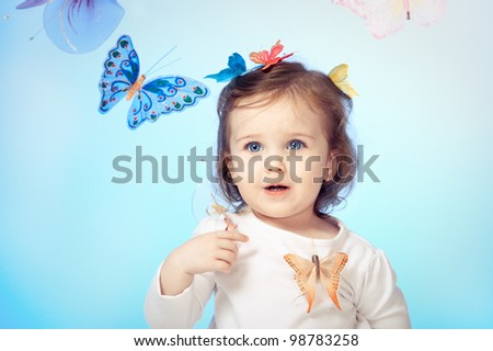 Laughing little girl with butterflies all around - stock photo