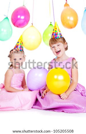 Laughing little girls in party hats holding balloons in hands - stock photo