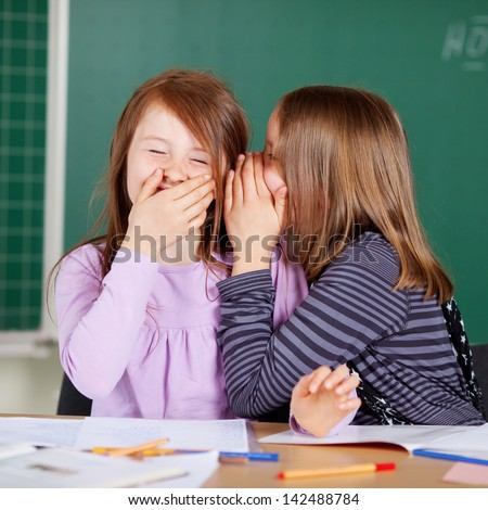 Laughing little girls sharing secrets in class sitting in front of the blackboard whispering to each other - stock photo