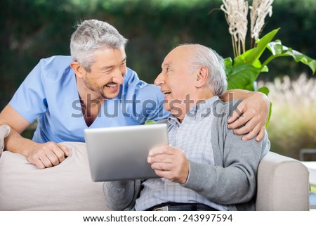 Laughing male caretaker and senior man using tablet computer at nursing home porch - stock photo