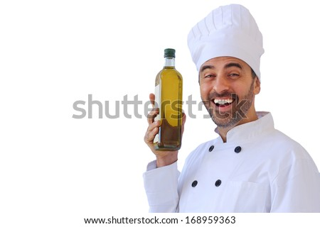 Laughing male chef or baker in a white toque and uniform holding up a bottle of healthy olive oil, isolated on white
