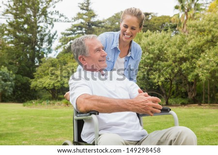Laughing man in wheelchair and daughter talking on a sunny day in park - stock photo