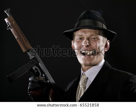 Laughing man like a chicago gangster with submachine gun - stock photo