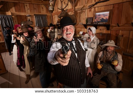 Laughing man with old west gang point guns in a saloon