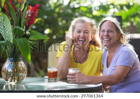 Laughing middle aged Caucasian female friends at table - stock photo