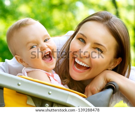 Laughing Mother And Baby outdoors. Nature. Beauty Mum and her Child playing in Park together. Outdoor Portrait of Smiling and Happy family. Joy. Mom and Baby - stock photo