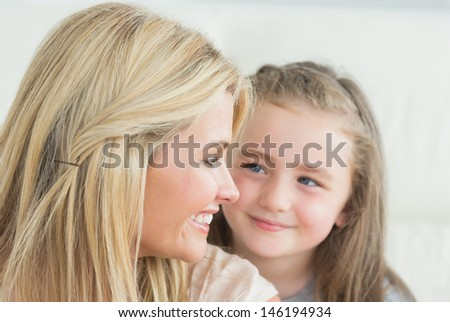 Laughing mother and daughter looking at each other - stock photo