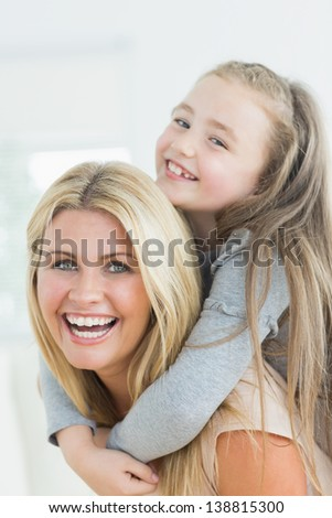 Laughing mother and daughter on her mothers back - stock photo