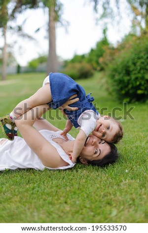 laughing mother and her daughter on grass - stock photo