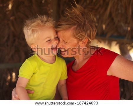 laughing mother and son hugging each other in a small beach house - stock photo