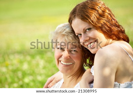Laughing mother and the daughter sit in embraces on a lawn - stock photo