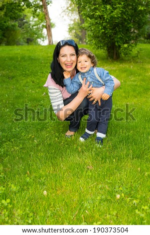 Laughing mother and toddler boy having fun in grass - stock photo