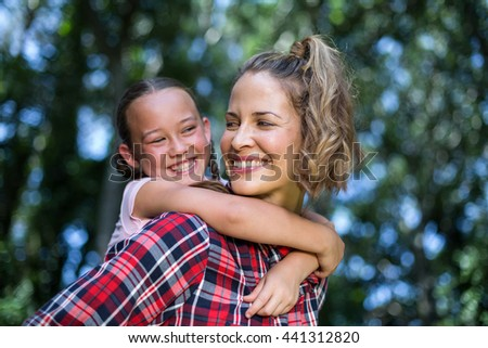 Laughing mother carrying daughter while looking at her in back yard - stock photo