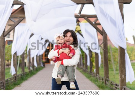 laughing mother embracing cute child - stock photo