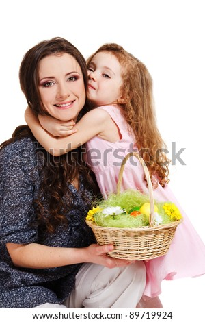 Laughing mother holding easter basket, daughter embracing her - stock photo