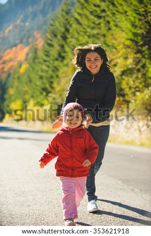 laughing mother running after daughter - stock photo