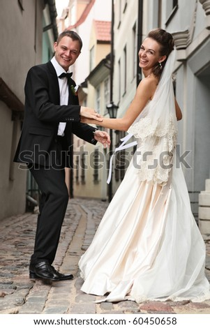 laughing newly wedded couple in old city - stock photo