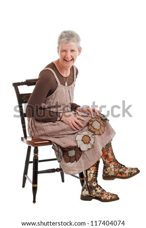 Laughing older woman with short gray hair sits sideways on chair and leans forward. She wears flowered boots and brown cotton shift dress. Isolated on white background, vertical, copy space.