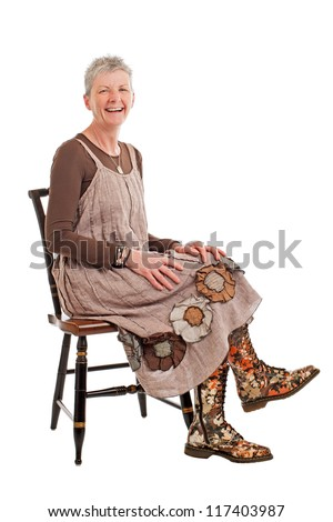 Laughing older woman with short gray hair sits sideways on chair. She wears flowered boots and brown cotton shift dress. Isolated on white background, vertical, copy space.