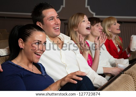 Laughing people in a cinema or theater watching a movie or a play - stock photo