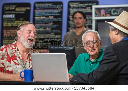 Laughing people in a coffee house with laptop - stock photo