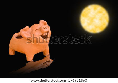 Laughing pig statue on full moon light - stock photo